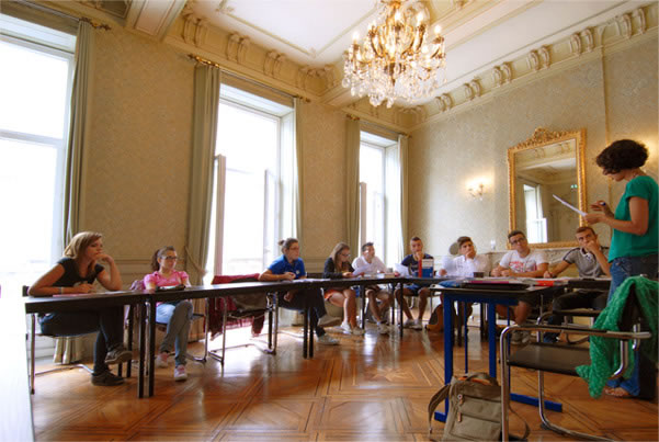 a french classroom with a chandelier hanging from the ceiling