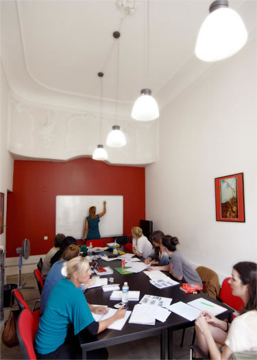 a high ceilinged classroom with students around a table