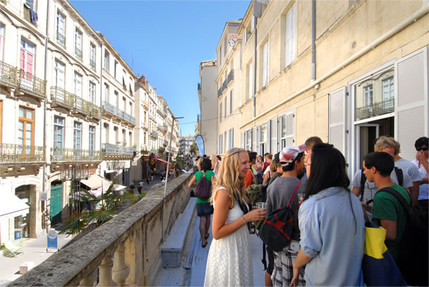 young people mixing and chatting on a terrace with a view of french buildings