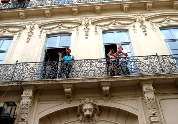 Students waving to their friends from the balcony of an old 18th century French building