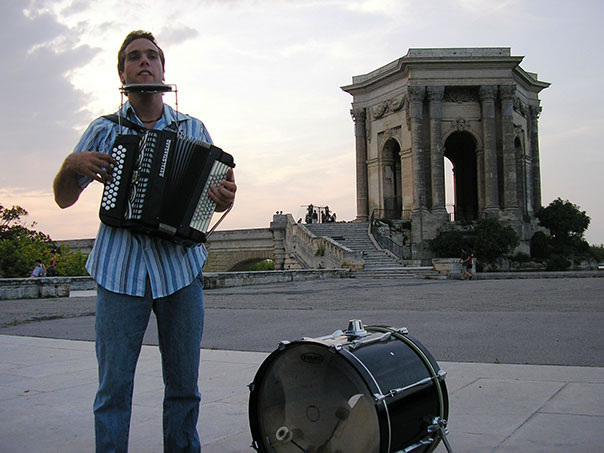 A musician playing the accordion, harmonica and drum in parc de Peyrou